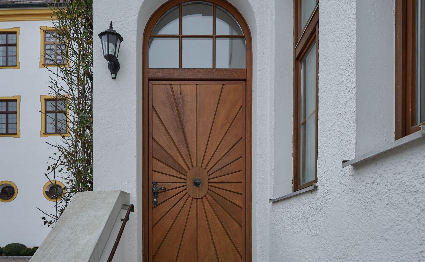 Eingangstüre aus Holz mit Oberlicht und Rundbogen