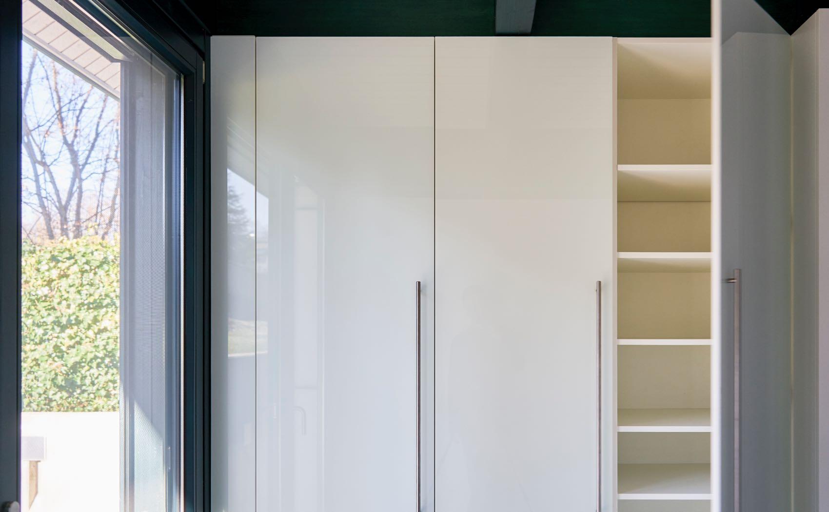 Schrankwand auf Maß mit weiß lackierter Glasfront